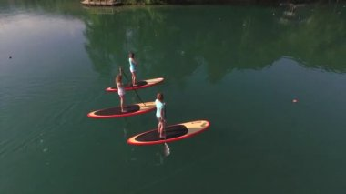 AERIAL: Flying above surfer girlfriends SUP boarding on Bled lake in beautiful morning — Stock Video