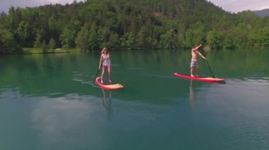AERIAL: Boyfriend and girlfriend stand up paddling on SUP boards — Stock Video