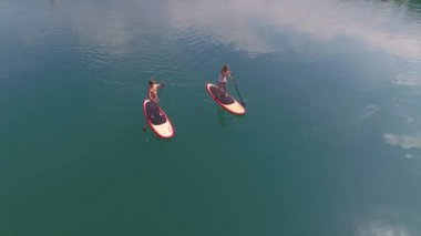 AERIAL: Surfer man and woman SUP boarding from lake island — Stock Video