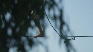 CLOSE-UP: Slacker man balancing and falling off a slackline — 图库视频影像