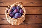 Organic ripe plums in a basket — Stock fotografie