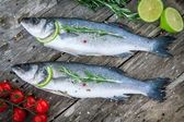 Two raw seabass with lime, cherry tomatoes and rosemary  — Stock Photo