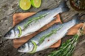 Two raw seabass with lime and rosemary — Stock Photo