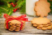 素朴な木製の背景に赤いリボンでクリスマスのジンジャーブレッドのクッキー — ストック写真