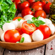 Mozzarella, organic cherry tomatoes, fresh basil and olive oil — Stock Photo #65461399