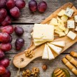 Cheese plate: Emmental, Camembert cheese, blue cheese, bread sticks, walnuts, hazelnuts, honey, grapes — Stock Photo #67248559