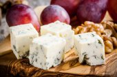Blue cheese close-up with grape and nuts on a wooden board — Stock Photo