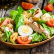 Caesar salad with croutons, quail eggs, cherry tomatoes and grilled chicken in wooden plate — Stock Photo #68589429