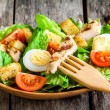Caesar salad with croutons, quail eggs, cherry tomatoes and grilled chicken in wooden plate — Stock Photo #68589871