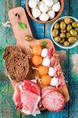Mozzarella, jamón serrano, canapés de melón con salami, olivas y pan — Foto de Stock