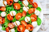 Salad of mozzarella, cherry tomatoes and spinach with balsamic sauce closeup — Stock Photo