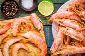 Fresh shrimps on wooden board with salt, pepper, lime closeup — Stock Photo