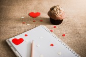 Chocolate muffin and  hearts on sackcloth textures — Stock Photo