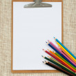 Wooden clipboard and colored pencils on old sackcloth background — Stock Photo #63280927
