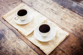 Two cups of coffee on brown napkin — Stock Photo