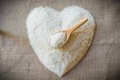 Rice laid out in a heart shape on sackcloth with wooden spoon — Stock Photo