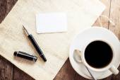 Blank card with pen and cup of coffee — Stock Photo