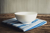 White bowl on a napkin. on wooden tabletop — Stock Photo