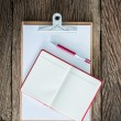 Old clipboard, red notebook, red pen on grungy wooden surface — Stock Photo #73098563