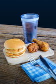 Chicken hamburger and fried chicken, glass of cola on wooden cut — Stock Photo