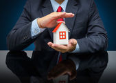Businessman holding a model house — Stock Photo