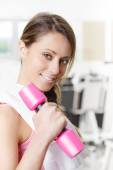 Smiling young woman weightlifting at the gym — Stock Photo