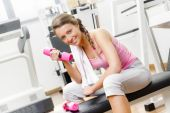 Smiling young woman weightlifting on the bench — Stock Photo