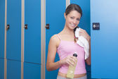 Fitness young smiling woman resting in blue dressing room — ストック写真