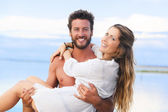Man holding woman in his arms under a blue sky on seaside backgr — Stock Photo