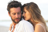 Woman embracing her man from behind on seaside background — Stock Photo