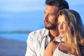 Man embracing his woman from behind on seaside background under — Stock Photo