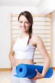 Young Fitness Woman Holding a Blue Mat at the Gym — Stock Photo