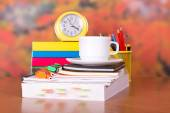 Clock and writing-materials on a table — Stockfoto