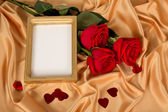 Roses in a and a frame on a cloth — Stock Photo