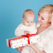 Woman holding baby with christmas presents — Stock Photo #55001081