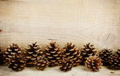 Bottom line horizontal pine cones christmas on wooden — Stock Photo