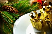 Closeup Christmas plate golden gifts pines wooden surface — Stok fotoğraf
