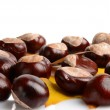 Horizontally many chestnuts with autumn leaves on white background — Stock Photo #58414593