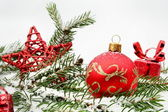 Red christmas gifts,baubles with red star and needles fir on sno — Stock Photo