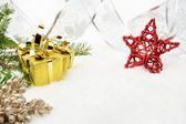 Gold christmas gifts with silver ribbon and needles fir with red — Stock Photo