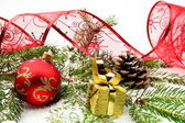 Golden christmas gifts,baubles with red ribbon and needles fir o — Stock Photo