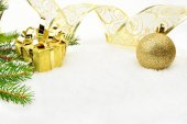 Golden christmas baubles with and needles fir and ribbon on snow — Fotografia Stock
