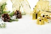 Zlaté vánoční dárky, sněhové vločky s zlatou stuhu a jehličí jedle — Stock fotografie