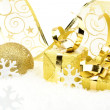Golden christmas baubles, gifts,snowflakes with golden ribbon on snow — Stock Photo #58525317