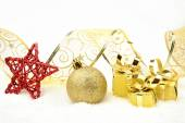 Golden christmas gifts,bauble ribbon on snow — Stock Photo