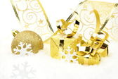 Golden christmas baubles, gifts,snowflakes with golden ribbon on snow — Stock Photo
