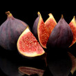 Three figs split like flower isolated on black background — Stock Photo #58793327
