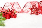 Red Christmas star and needles fir and ribbon on snow — Stock Photo