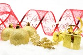 Golden christmas gifts,baubles red ribbon on snow — Stock Photo