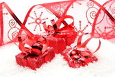 Three red christmas gifts with ribbon on snow — Stock Photo